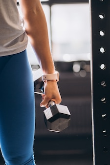Schlankes sportliches mädchen führt körperliche übungen mit hanteln durch.