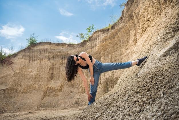 Schlankes sportliches mädchen in einer freizeitkleidung, die gegen die felsen des sandes im steinbruch aufwirft. sommerzeit Premium Fotos