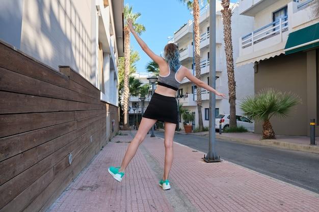 Schlankes sportmädchen teenager mit rücken, frau mit offenen armen auf einem bein, sport treiben, spaß haben. aktiver, sportlicher, gesunder lebensstil, jugendliche teenager