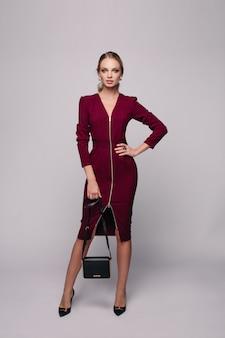 Schlankes, stylisches model im kleid mit handtasche.
