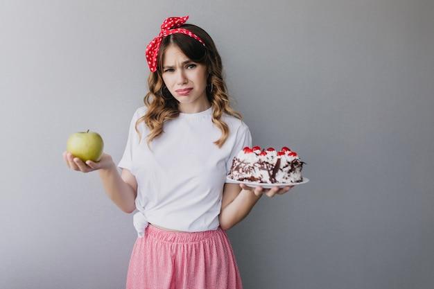 Schlankes trauriges mädchen, das früchte und kuchen hält. das charmante lockige weibliche model kann sich nicht entscheiden, was es essen soll.