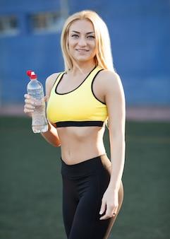 Schlankes trinkwasser der jungen frau nach dem training