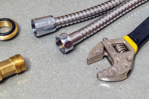 Schlauch und verstellbarer schraubenschlüssel in wassertropfen