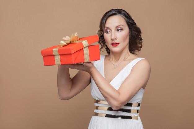 Schlaue, elegante, brünette frau mittleren alters im weißen kleid, die die rote geschenkbox hält und in sie schaut. emotions- und gefühlskonzept. studioaufnahme, drinnen, auf hellbraunem hintergrund isoliert