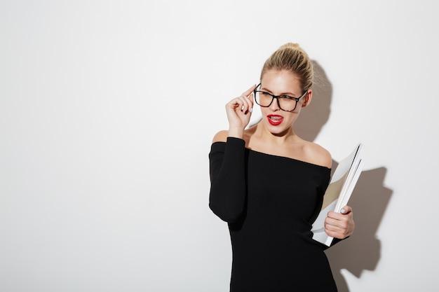 Schlaue geschäftsfrau im kleid und in brillen, die dokumente verwahren