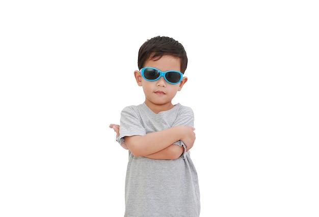 Schlauer asiatischer kleiner junge verschränkte die arme und trug sonnenbrille auf weiß