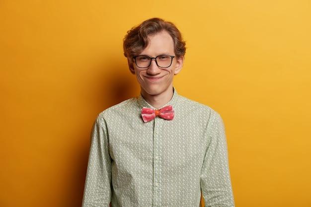 Schlauer hipster mann sieht geheimnisvoll aus, hat ein breites lächeln, einen schönen plan, wie man erfolg hat, trägt eine brille, ein elegantes hemd mit fliege, zufrieden mit den ergebnissen des vorstellungsgesprächs, isoliert auf gelb