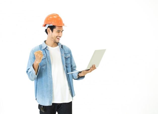 Schlauer junger asiatischer architekt ingenieur mann tragen lässige jeans und orange schutzhelm, die hände halten laptop, um seine geplante arbeit mit glücklicher und erfolgreicher position zu überprüfen