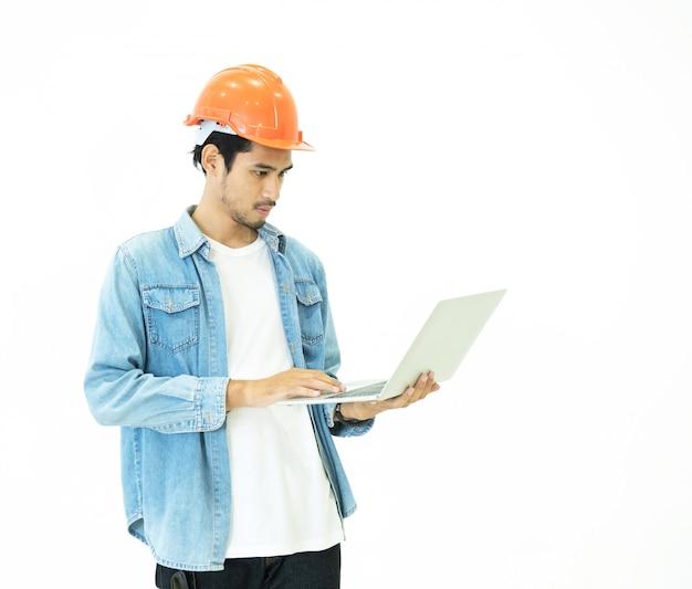 Schlauer junger asiatischer architekt ingenieur mann tragen lässige jeans und orange schutzhelm, die hand halten laptop, um seine planarbeit mit ernsthafter und denkender position zu überprüfen