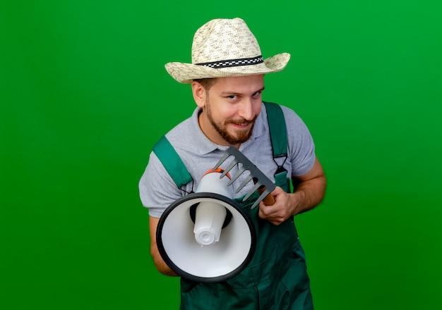 Schlauer junger hübscher slawischer gärtner in der uniform und im hut, die lautsprecher und rechen halten, die lokal auf grüner wand mit kopienraum suchen