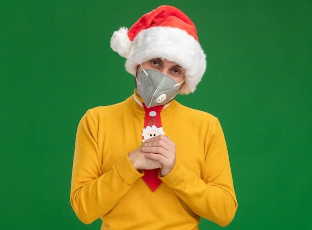 Schlauer junger kaukasischer mann, der weihnachtshut und krawatte mit schutzmaske trägt, hält hände zusammen, die kamera lokalisiert auf grünem hintergrund betrachten