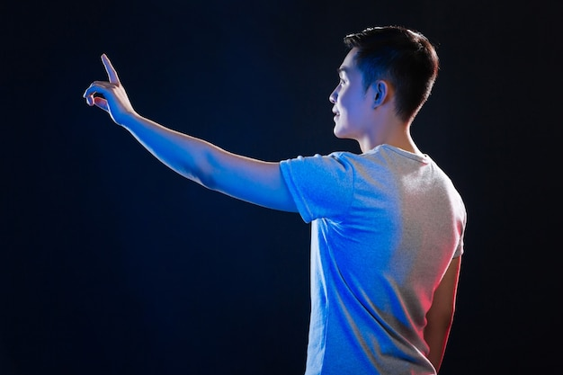Schlauer junger mann, der den sensorischen bildschirm verwendet, während er gegen schwarzen hintergrund steht