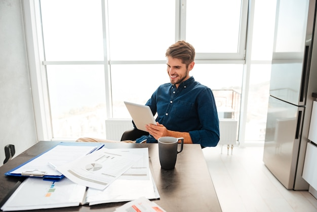 Schlauer junger mann, der tablette betrachtet und nahe tisch mit dokumenten der hausfinanzen und der tasse kaffee sitzt