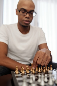 Schlauer junger schwarzer mann, der zu hause schach spielt und den ersten satz macht