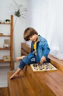 Schlauer kleiner junge, der schach auf dem schachbrett im raum spielt