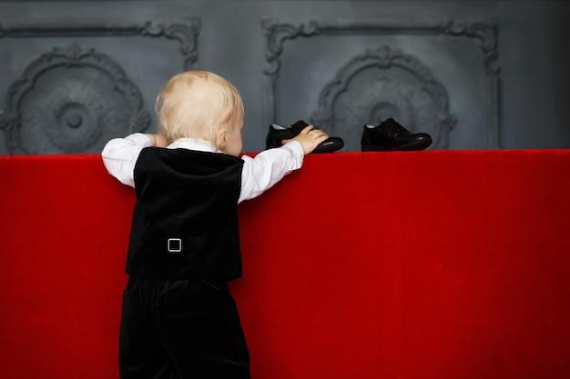 Schlauer kleiner junge, der versucht, lackschuhe zu tragen