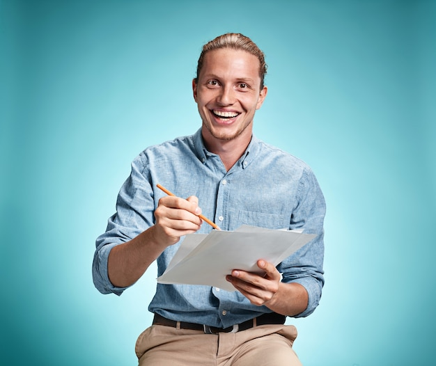 Schlauer lächelnder student mit großer idee, die blätter des papiers hält
