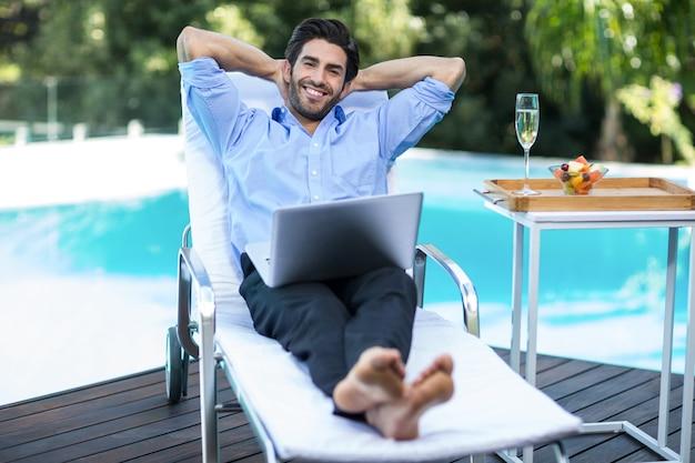 Schlauer mann mit einem laptop, der auf sonnenliege entspannt