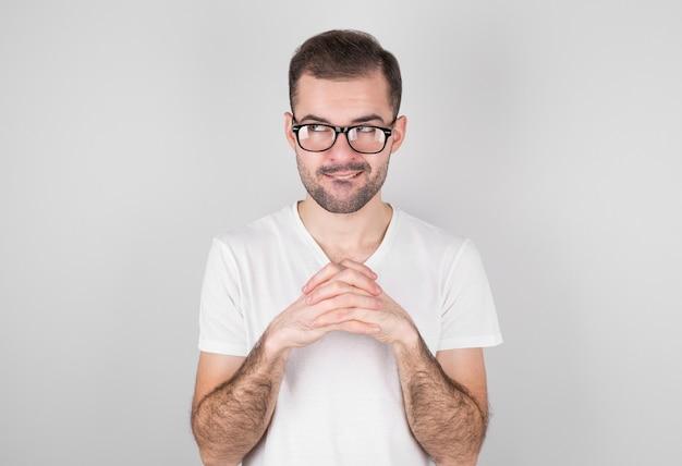Schlauer mann verzieht das gesicht, hält die handflächen zusammen, der typ hat einen guten plan zu realisieren, der grausame mann wartet auf etwas. nahaufnahme porträt, rache konzept.