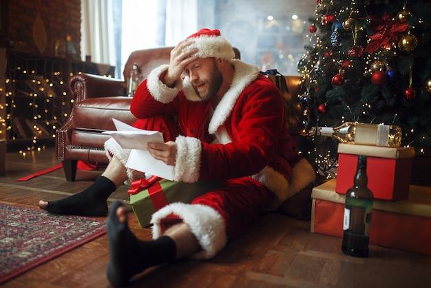 Schlecht betrunkener weihnachtsmann liest briefe unter weihnachtsbaum