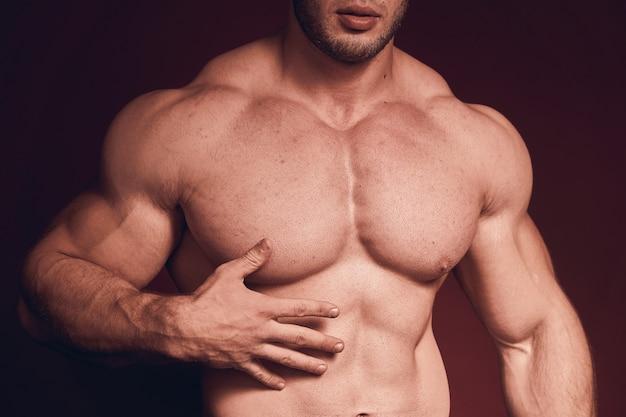 Schlecht rasierter muskulöser mann. großer brustmuskel. der körper eines bodybuilders.
