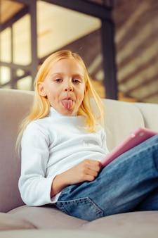 Schlechte angewohnheit. fröhliches kind, das auf einem gemütlichen sofa sitzt und direkt in die kamera schaut