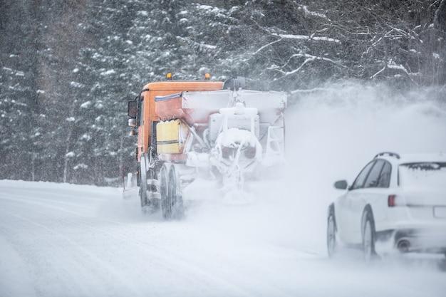 Schlechte sicht auf die straße eines autos, das während des winterdiensts direkt hinter einem schneepflug fährt.