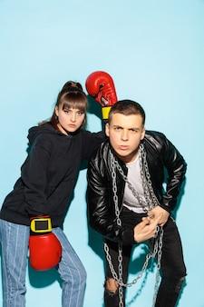 Schlechte spiele. schließen sie herauf modeporträt von zwei jungen coolen hipster-mädchen und jungen, die jeans tragen. zwei ernste beste freunde, die spaß über blauer wand haben.