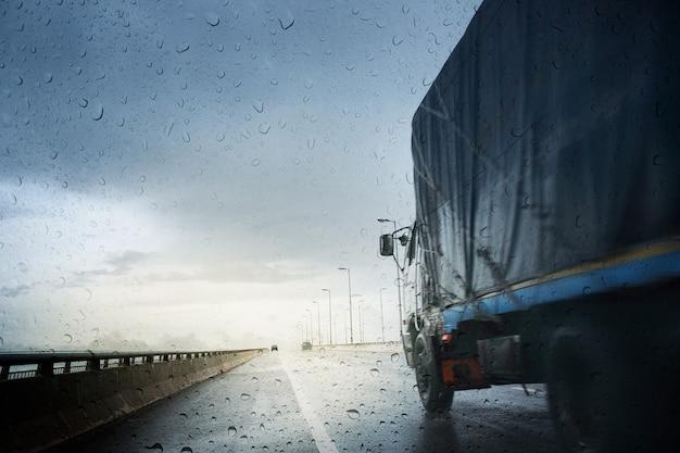 Schlechte wetterbedingungen auf der straße während des regensturms, blick durch die windschutzscheibe des regnerischen tages. selektiver fokus und farbe getönt.