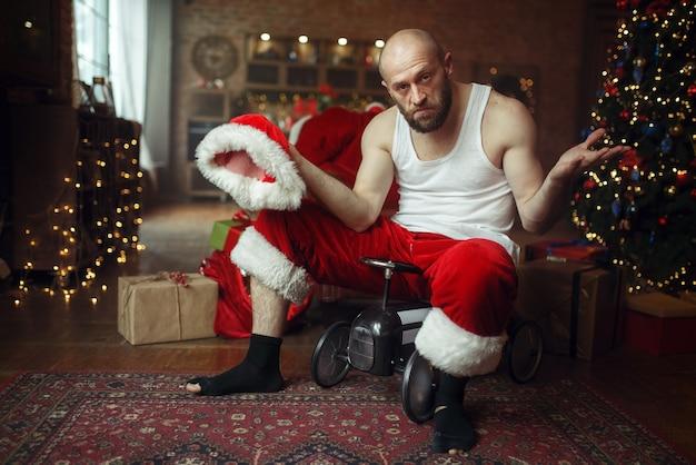 Schlechter betrunkener weihnachtsmann im roten hut, der auf kleines spielzeugauto reitet