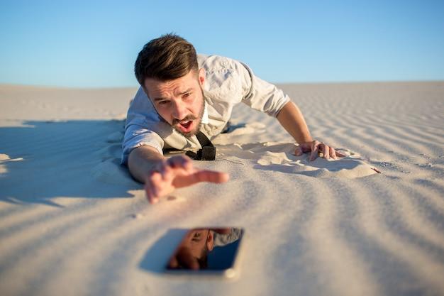 Schlechter empfang. geschäftsmann, der nach handysignal in der wüste sucht