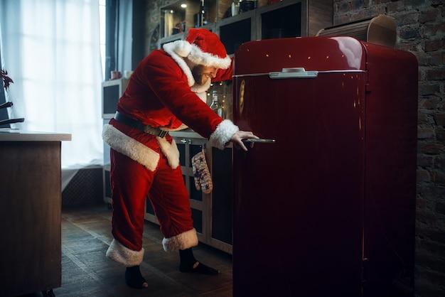 Schlechter frecher weihnachtsmann öffnet den kühlschrank