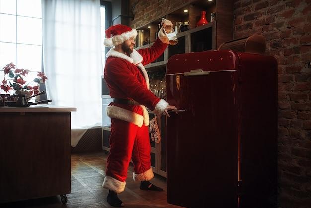 Schlechter frecher weihnachtsmann stiehlt alkohol aus dem kühlschrank
