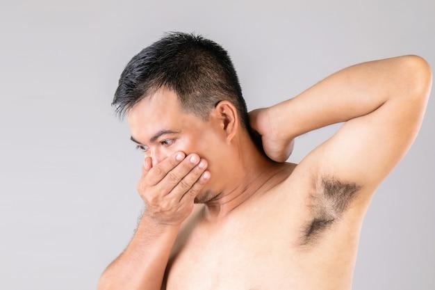 Schlechter geruch achselausschlag: mann überprüft und riecht seine achselhöhle.
