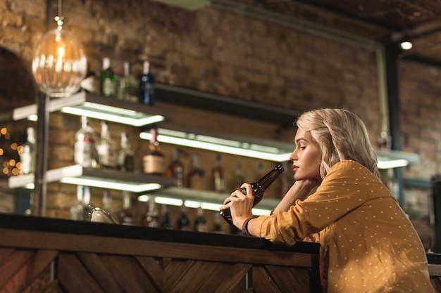 Schlechter tag. hübsche blonde frau, die an der bartheke sitzt und bier sickert, während sie mit etwas verärgert ist