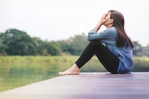 Schlechter tag-konzept. traurigkeit-frau, die durch den fluss auf hölzerner patio-plattform sitzt