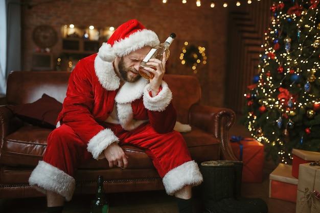 Schlechter weihnachtsmann mit flasche alkohol, der auf couch sitzt