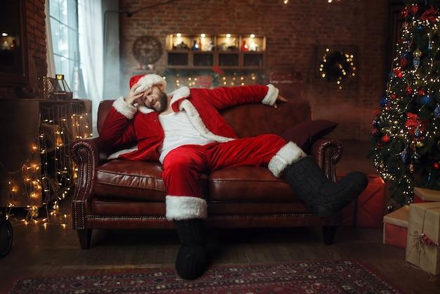 Schlechter weihnachtsmann mit kater, der auf couch sitzt
