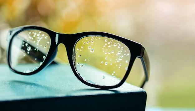 Schlechtes anblick-konzept. viele tröpfchen auf brillen unterbrachen die menschlichen augen