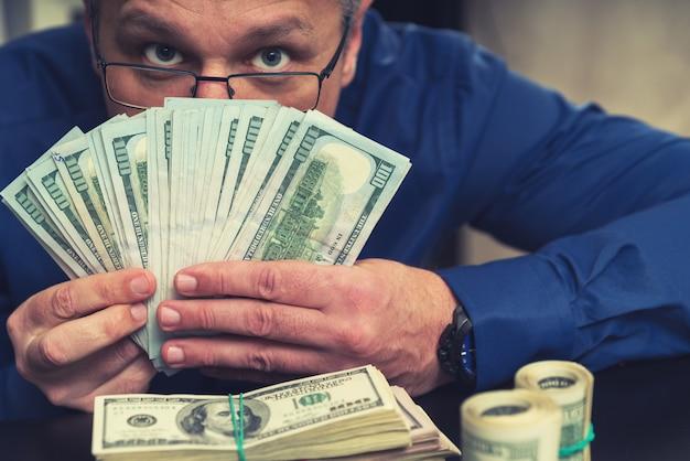 Schleichender geschäftsmann, der sich hinter einer handvoll dollarnoten versteckt