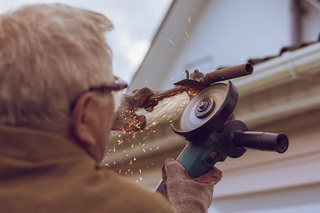 Schleifernahaufnahme schneidet metall mit funken
