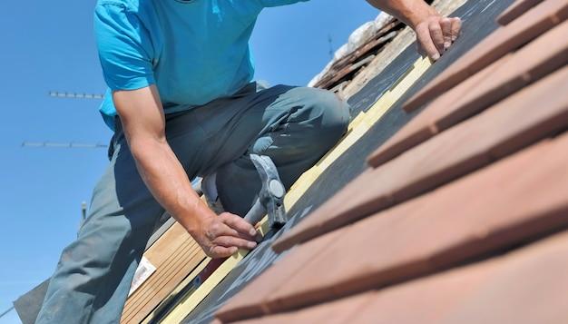 Schließen sie auf einer arbeitskraft, die einen hammer hält und ein dach eines hauses erneuert