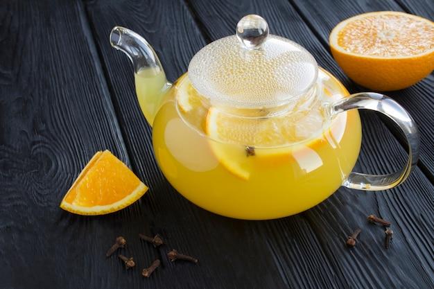 Schließen sie auf tee mit orange und nelken in der glasteekanne