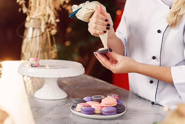 Schließen sie bäckerhände mit süßwarenbeutel, der creme zu macarons muscheln drückt.