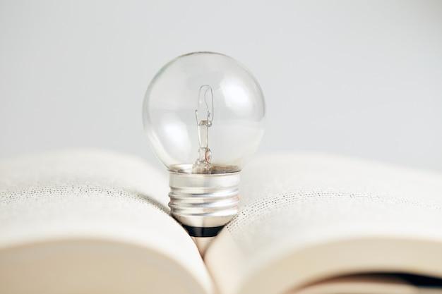 Schließen sie bis zu einer glühbirne auf geöffnetem buch. kreatives und pädagogisches konzept.