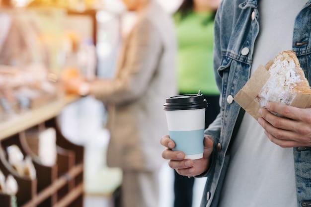 Schließen sie das bokeh-bild eines mannes in einer jeansjacke, der eine tasse kaffee und ein croissant in einer papierverpackung hält.