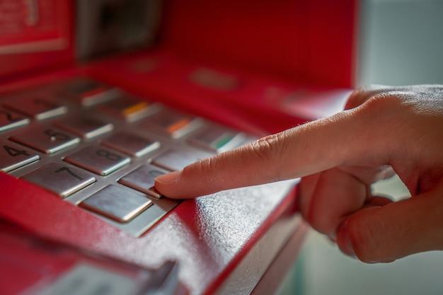 Schließen sie das drücken von hand und verbergen sie den geheimcode, wenn sie das geld über einen geldautomaten abheben