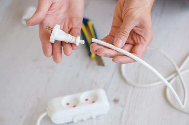 Schließen sie das elektrische europäische verlängerungskabel, die steckdosenleiste und die steckdosen, die männlichen elektrikerhände halten den abgeschnittenen kabeldraht