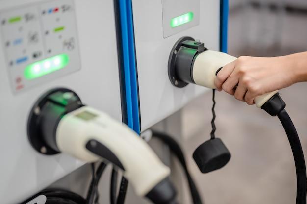 Schließen sie das ladegerät an die stromversorgung an. für fahrzeuge, die zum fahren mit elektrischem strom fahren./ grünes licht-status volle batterie.