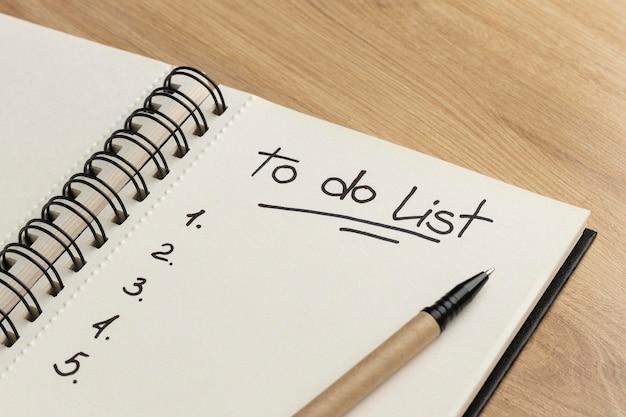 Schließen sie das notizbuch mit der aufgabenliste auf dem schreibtisch